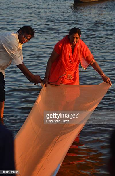 Devotees making and offering saree in Ganga, in Kumbh mela area, on February 7, 2013 in Allahabad, India.The mega religious fair is held once in 12...