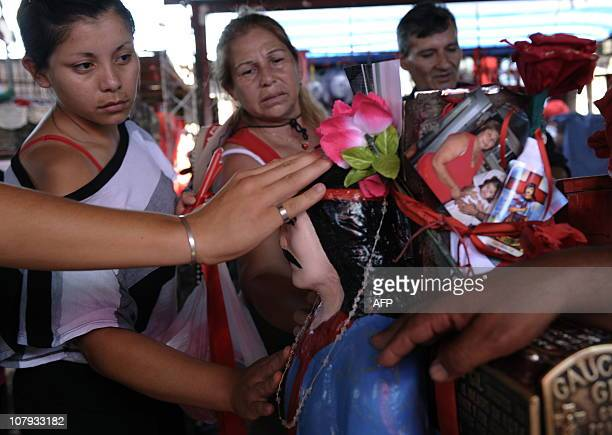 Devotees of folk saint Gauchito Gil touch his image at the sanctuary near Mercedes in the Argentine province of Corrientes on January 8 2011 The cult...
