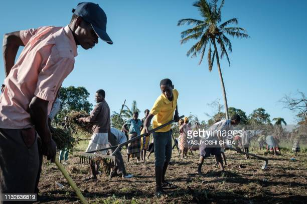 Devotees of Jehovah's Witnesses clear the land to prepare for installing more tents at an evacuation site where already 352 people stay after the...