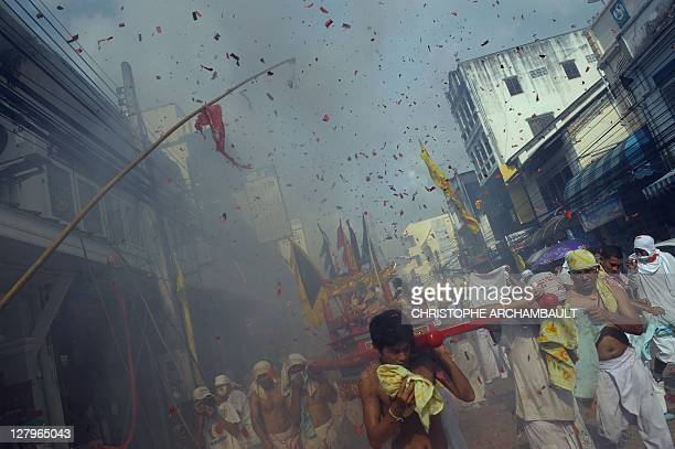 Devotees of the Chinese Bang Neow Shrine carry an idol on a palanquin as firecrackers explode during a street procession to mark the annual...