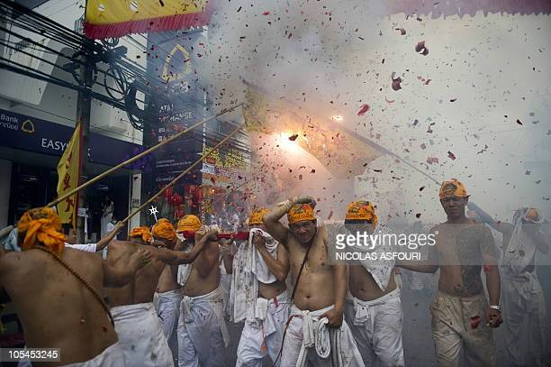 Devotees of the Chinese shrine of Jui Tui carry a Chinese god on a palanquin as firecreckers explode during a procession to mark the annual...
