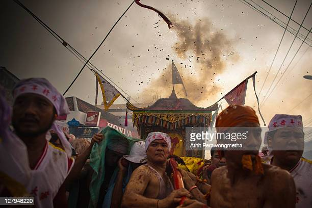 Devotees of the Chinese shrine of Kathu Shrine carry a Chinese God on a palanquin as firecreckers explode during a procession at the Vegetarian...