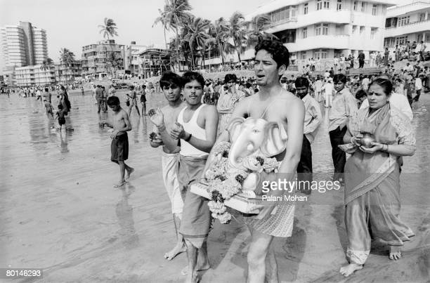 Devotees of the elephant god Ganesha carry statues of the deity to be immersed into the water at Chowpatty Beach October 2002 in Mumbai India Lord...