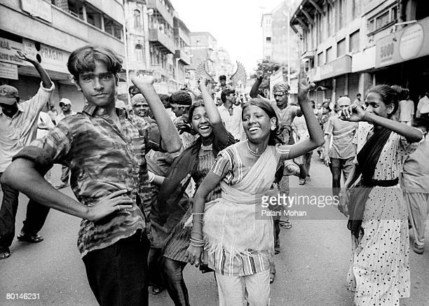 Devotees of the elephant god Ganesha dance in the streets as they carry statues of the deity to be immersed in the water October 2002 in Mumbai India...