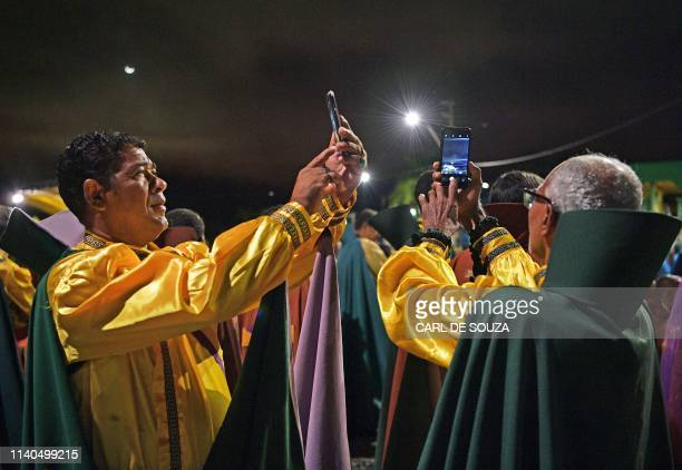 Devotees of the Vale do Amanhecer religious community, take selfies during their biggest ceremony of the year at their temple complex in Vale do...