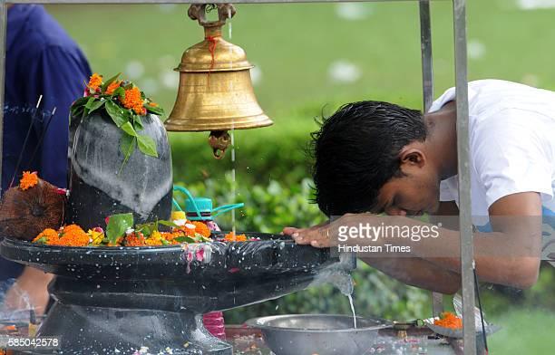 Devotees offer milk, honey, Gangajal, curd and coconut water on a Shivling, on the morning of Savan Shivratri festival at Shiv Murti Rangpuri on...