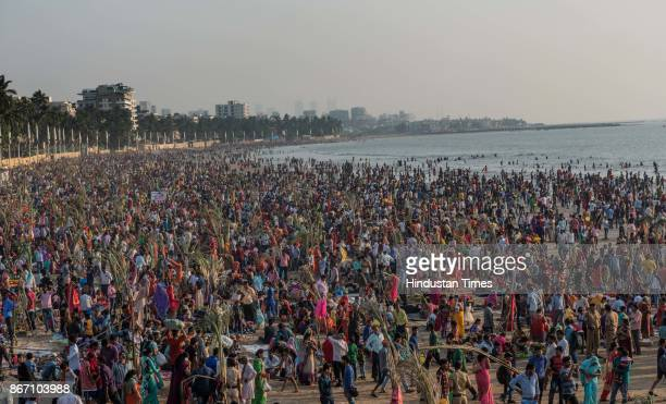 Devotees offer prayers at Juhu Beach during the sunset to mark Chhath Puja festival on October 26 2017 in Mumbai India Thousands of devotees...