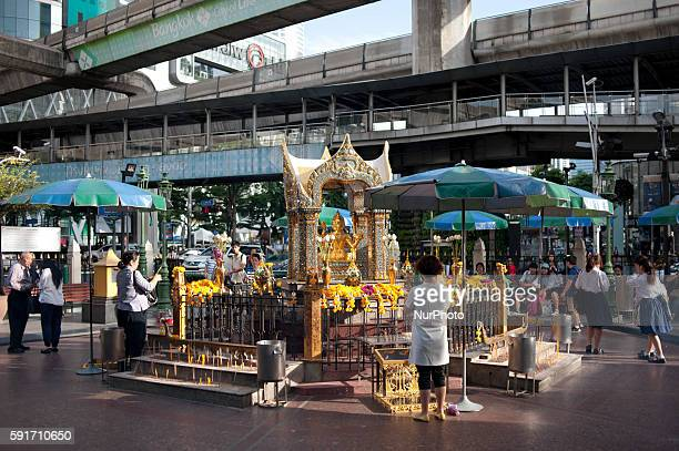 Devotees offer prayers at the Erawan Shrine, a popular tourist landmark in Bangkok on August 17 the eve of the first anniversary of a bomb attack...