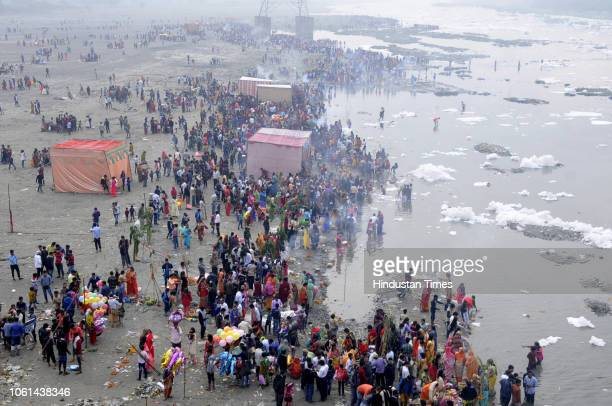Devotees offer their prayers at Kalindi Kunj on the occasion of Chhath Puja on November 14 2018 in Noida India Thousands of devotees celebrating...