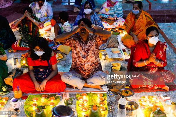 Devotees offering prayers next to lit candles during the festival. Every year, Hindu devotees mainly the followers of Lokenath Brahmachari, mostly...