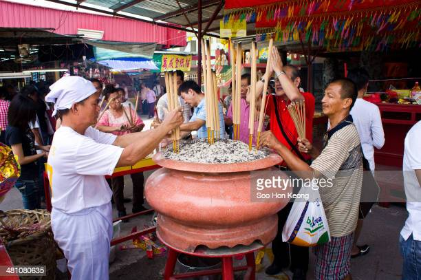 Devotees offerring incense and praying to the god during the annual Nine Emperor Gods Festival at Kau Ong Yah Temple, Ampang, Kuala Lumpur, Malaysia