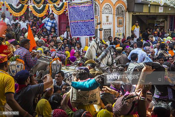 Devotees on their way to bath in Pushkar Lake merge with a procession showcasing artists and children dressed as various Gods and Godesses at a...