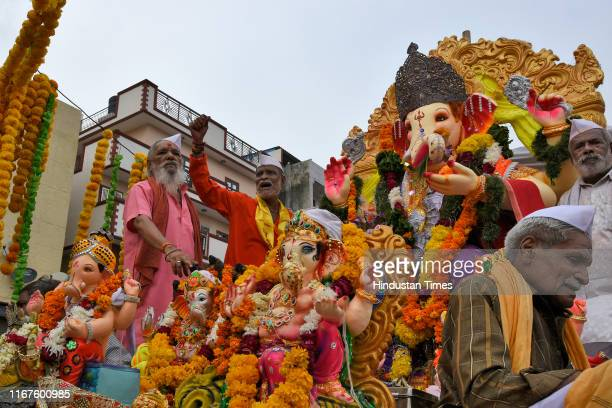 Devotees participate in a procession with the idols of Lord Ganesh for its immersion on the last day of the Ganesh Chaturthi festival at Kalkaji on...