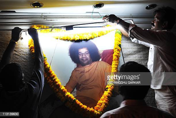 Devotees pay their respects in front of a picture of Hindu guru Satya Sai Baba outside Prashanthi Nilayam temple at the Puttaparthi village some 200...