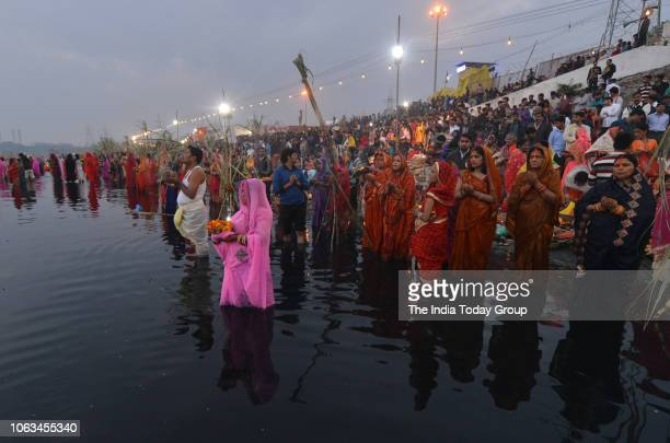 Devotees perform Chhath Puja rituals on the Yamuna river at Kalindi Kunj in New Delhi