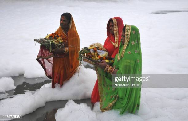 Devotees perform rituals in the polluted waters of Yamuna river at Kalindi Kunj on the occasion of Chhath Puja, on November 3, 2019 in Noida, India....