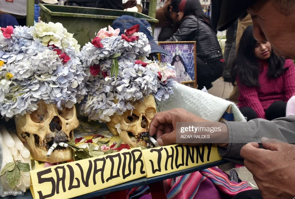 Devotees perform rituals with their 'natitas' (snub-nosed) human skulls, at the Central Cemetery of La Paz, on November 8, 2016. The natitas are meant to protect their owners, who keep them at home all year long and bring them to the cemetery chapels every 8 of November to perform rituals which end up in a traditional party. /