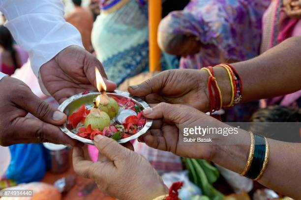 Devotees perform their ritual with flowers and lit up lamps.