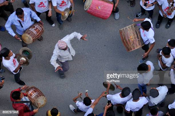 Devotees playing traditional drums as Locals carry and rotates top part of a chariot of Lord Narayan across the streets of Hadigaun during Lord...