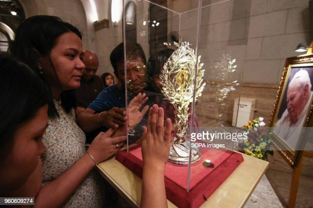 Devotees pray as they touch the glass encasement of the blood reliquary The Manila Cathedral in Intramuros displayed the blood relic of Pope John...