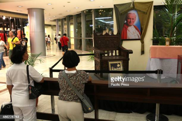 A devotees pray at front of a papal chair was used by Blessed John Paul II during his visit in Philippines at the activity area of Gateway Mall in...