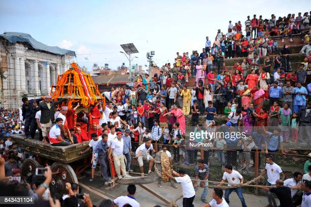 Devotees pulling the chariot of Goddess 'Kumari' living goddess of Kathmandu on the fourth day of Indra Jatra Festival celebrated at Basantapur...