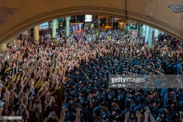 Devotees raises their hands as the Black Nazarene is being returned back to the Quiapo Basilica after a gruelling 20 hour procession on January 10...
