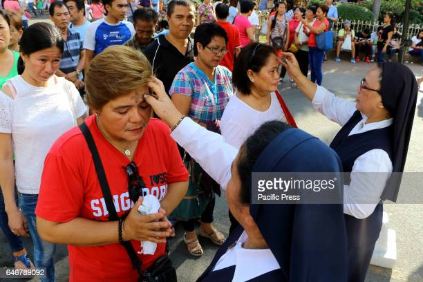 Devotees receiving ashes from the nun's of National Shrine of Our Mother of Perpetual Help also known as Redemptorist Church as part of the start of...