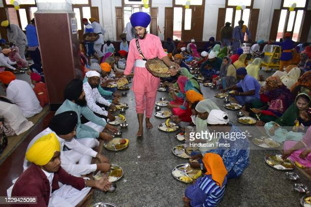 Devotees seated while langar meals are served at the Golden Temple on the occasion of birth anniversary of the fourth Sikh Guru Ramdas on November 2,...