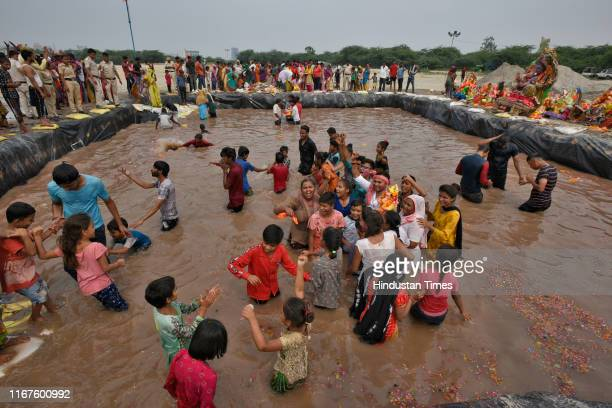 Devotees shout religious slogans during the immersion of Lord Ganesh at a temporary pond on the last day of the Ganesh Chaturthi festival, at Jaitpur...