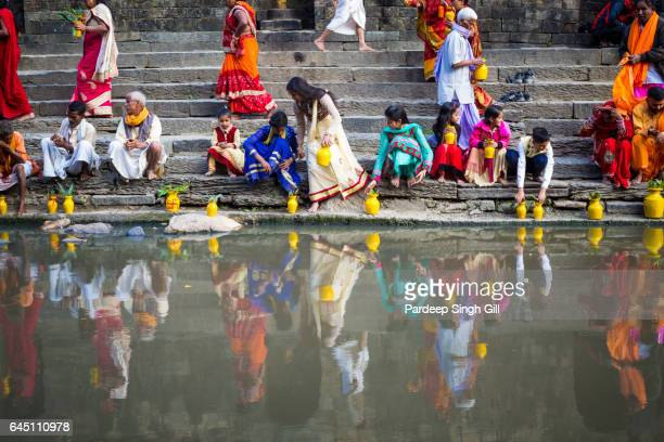 Devotees sit on the banks of the river at Pashupatinath temple in Kathmandu, Nepal.