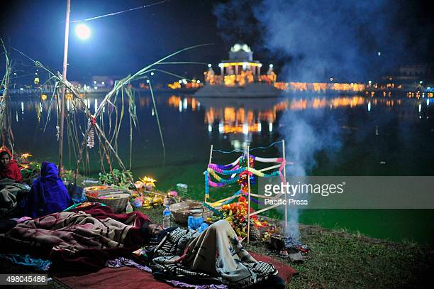 Devotees sleeps on the premises of Rani Pokhari on the 4th day of Chhath Puja Festival. Chhath Puja Festival, the worship of Sun God, is common in...