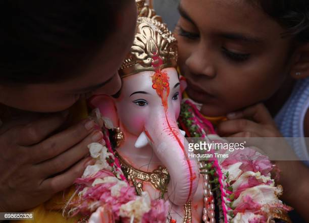 Devotees speak out their wishes to come true in Lord Ganesha's ears as a part of tradition while the idol is being taken for immersion on Day 2 of...