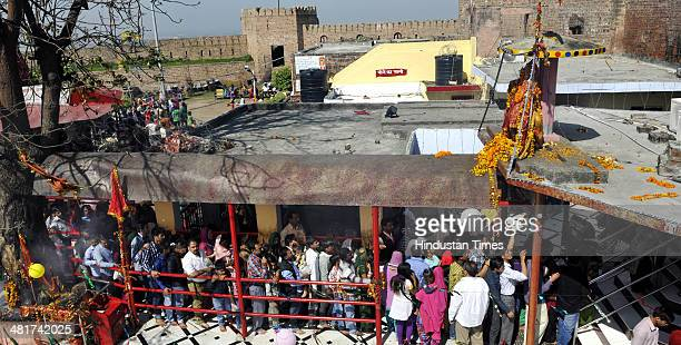 Devotees stand in a queue to offer prayers at a Kali Temple on the first day of the Navratra or nine nights festival on March 31 2014 in Jammu India...