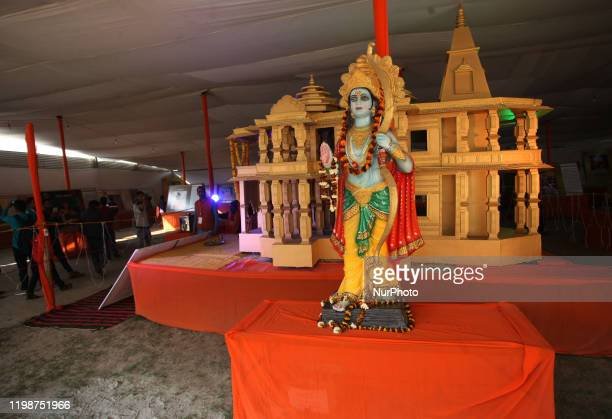 Devotees take pictures near a model of a proposed Ram Hindu temple is displayed at Vishwa Hindu Parishad camp in magh mela Allahabad on February...