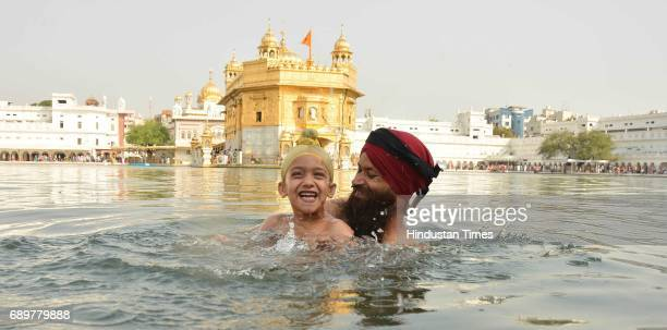 Devotees taking holy dip and paying obeisance at Golden Temple on the occasion of martyrdom of Guru Arjan Dev ji in Golden Temple on May 29 2017 in...