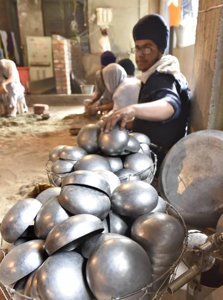 Devotees taking langar on Sarbloh Utensils at Rangla Sahib on April 25 2017 in Amritsar India Sarbloh is the metal used in the Bata used by Guru...