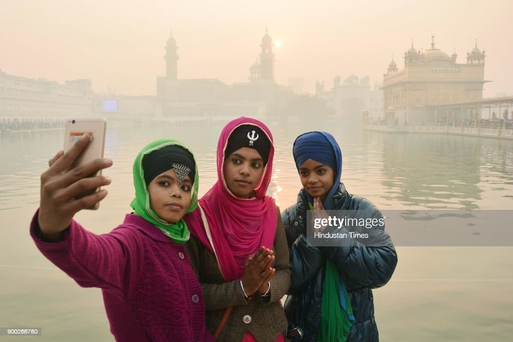 Devotees taking selfie during pay obesiance as the sun rises in the background on the first day of the New Year at Golden Temple on January 1 2018 in.