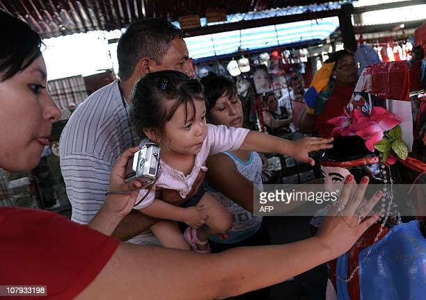 Devotees touch an image of folk saint Gauchito Gil at his sanctuary near Mercedes in the Argentine province of Corrientes on January 8 2011 The cult...