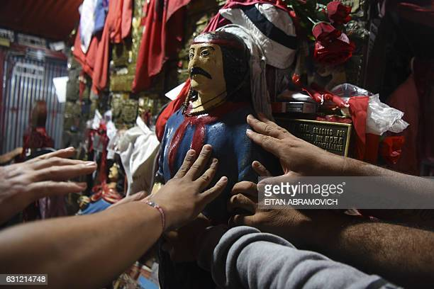 TOPSHOT Devotees touch an image of folk saint Gauchito Gil at his sanctuary near Mercedes in the Argentine province of Corrientes on January 8...