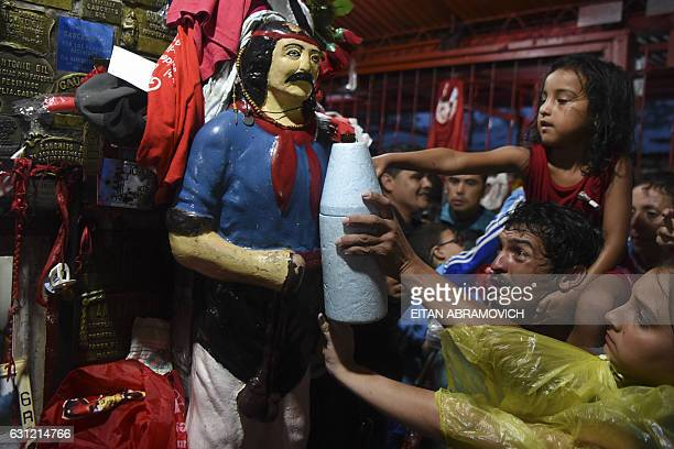 Devotees touch an image of folk saint Gauchito Gil at his sanctuary near Mercedes in the Argentine province of Corrientes on January 8 2017The cult...