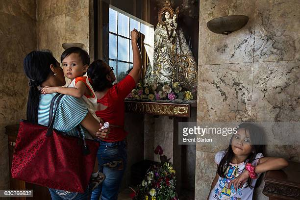 Devotees touch and kiss the glass housing an Ivory icon Our Lady of Manaoag in St Joseph's Cathedral Cebu Philippines January 13 2012 This devotional...