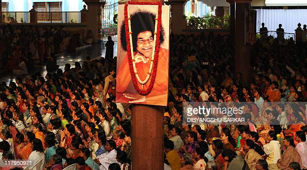 Devotees wait to pay homage after the final rituals of the burial of Hindu guru Sathya Sai Baba inside Prashanthi Nilayam in the village of...