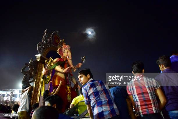 devotees waiting with idol's of the god ganesh at girgaon chowpatti before immersion - ganesh chaturthi stock photos and pictures