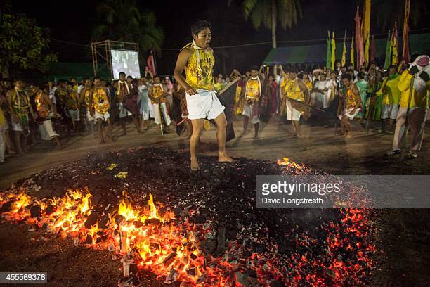 Devotees walk across hot coals at the Chinese shrine of Tae Gun Tae Tai during the annual Vegetarian Festival in Phuket Thailand The traditional...