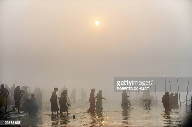 Devotees walk into the waters at the Sangham or confluence of the Yamuna and Ganges river during day break at the Kumbh Mela celebration in Allahabad...
