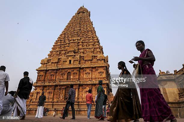 Devotees walk past the temple tower at the Brihadeshwara Temple in Thanjavur, Tamil Nadu, India, on Sunday, Oct. 16, 2016. India's new central bank...