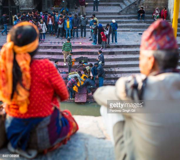 Devotees watch a cremation ceremony at Pashupatinath temple in Kathmandu, Nepal.