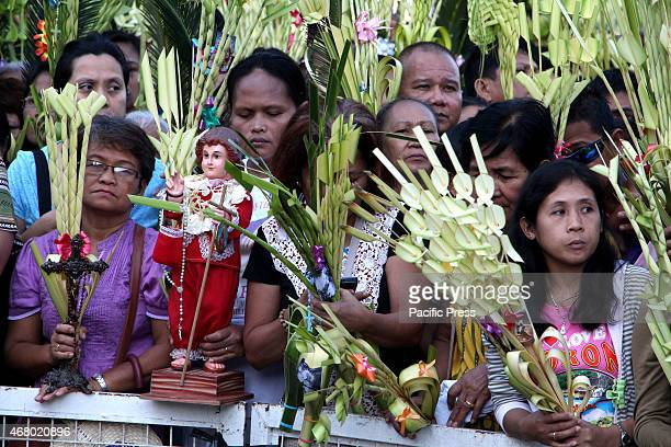 Devotees wave their 'palaspas' while being blessed by a priest in Antipolo City Cathedral during the celebration of Palm Sunday Palm Sunday is the...