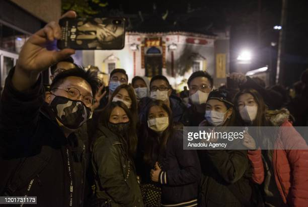 Devotees wearing a protective face masks take a selfie before entering the Lin Fa Kung temple during the Kwun Yum Treasury festival in Hong Kong...